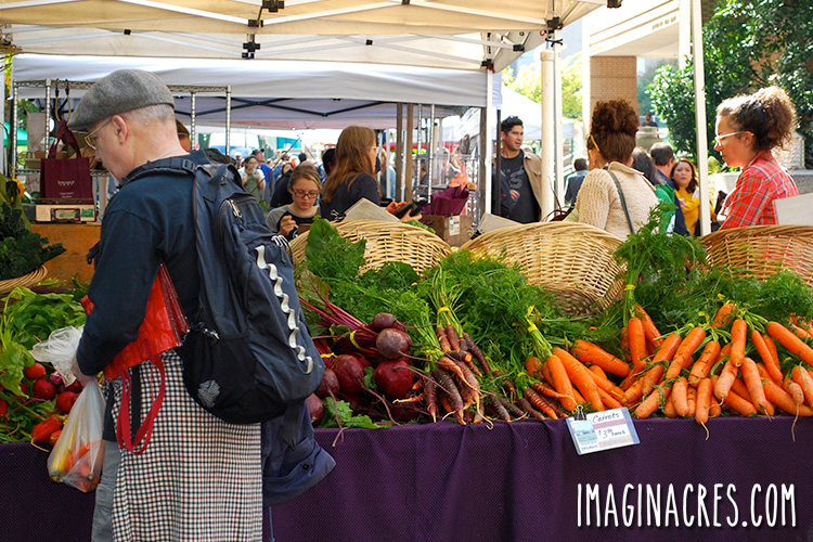 People walking around a farmers market table filled with produce.