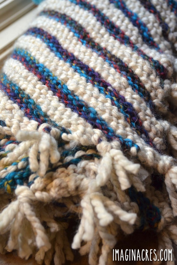 hand knitted striped baby blanket with fringe